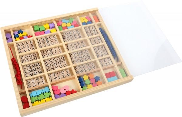 Buchstaben und Fädelperlen im Kasten